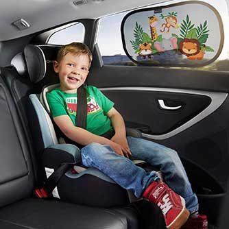 Kind im Auto mit Sonnenschutz an der Scheibe
