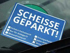 """Notizzettel """"scheisse geparkt"""" an der Windschutzscheibe"""